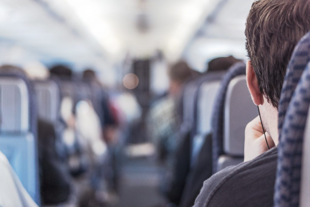 Man looking down aisle of plane with onboard social seating