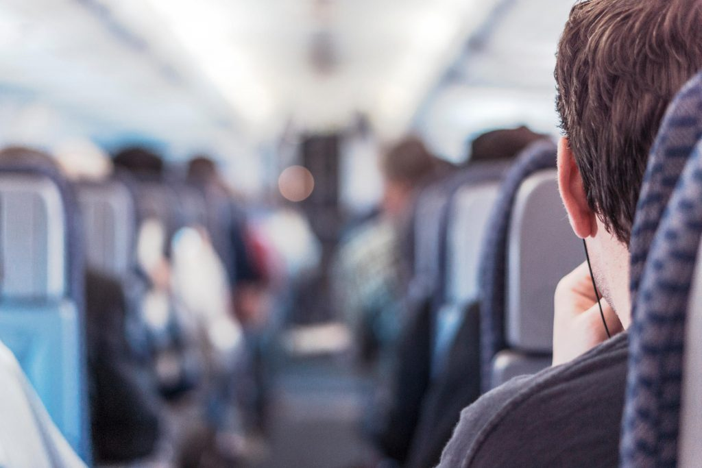 Man using onboard network looking down centre aisle of plane