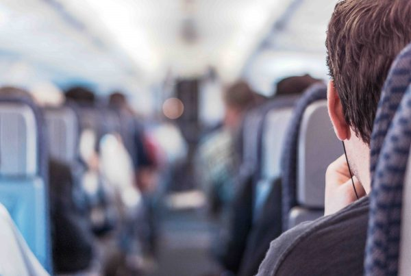 Man optimising journey looking down aisle of plane