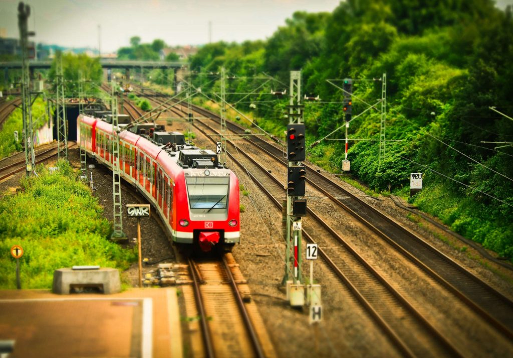 A red train with in-journey wifi exiting a tunnel