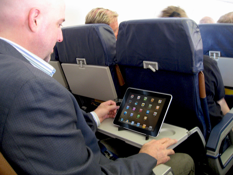 Bald man using official airline app on tablet mid-flight