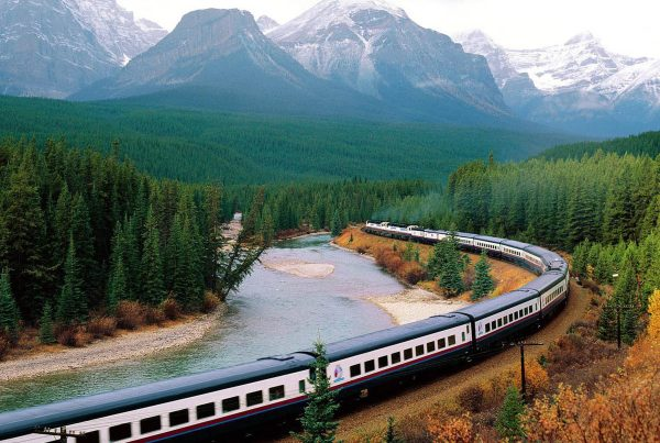 Train travelling across countryside by mountain and river