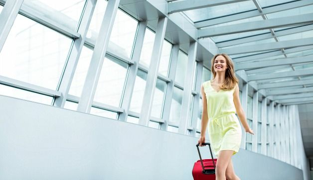 Woman in green dress walking with red suitcase to get her flight with in-journey wifi