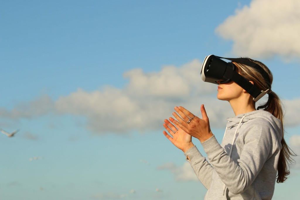 Woman using virtual reality headset on blue sky