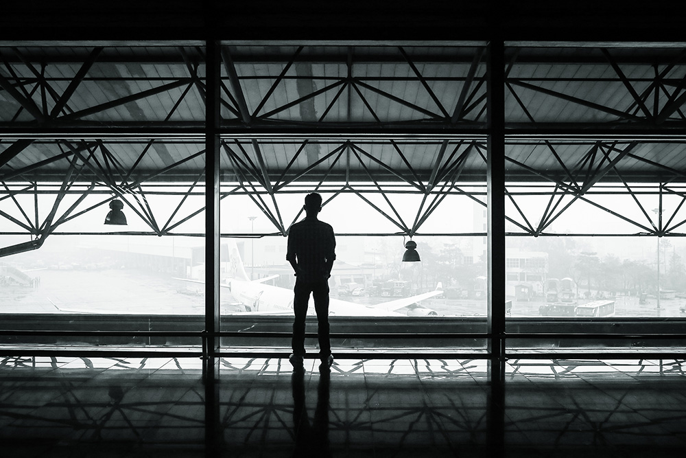 Man staring out of window at airport terminal in monochrome