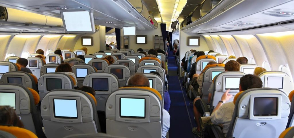 Passengers using social seating onboard a flight with seatback screens