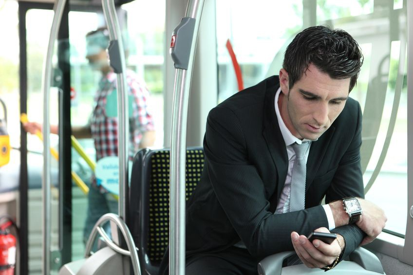 Man using his smartphone on a coach hire service