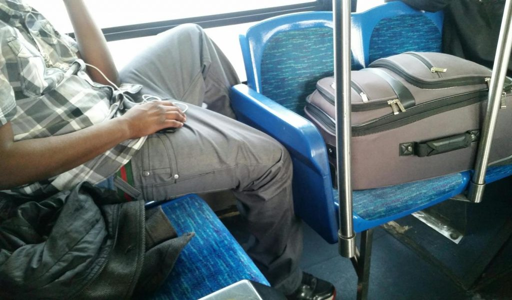 Passenger hoarding seats on public transport with bags