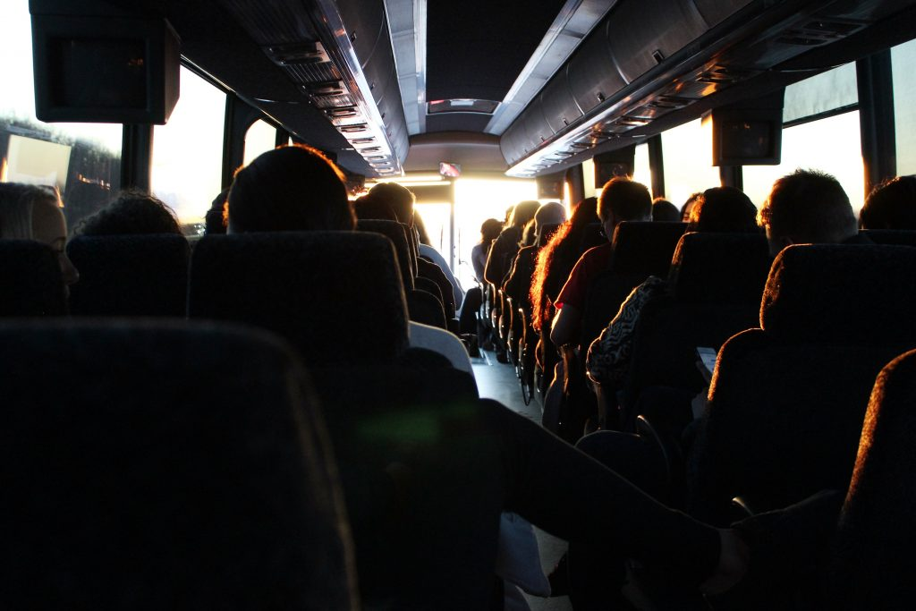 Crowded bus at sunset silhouettes
