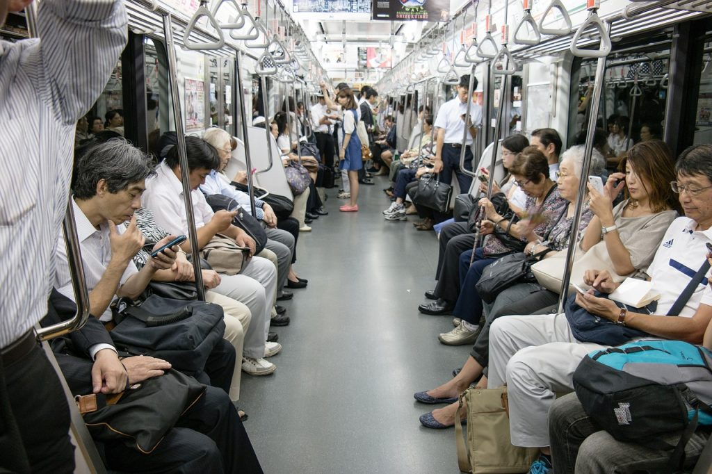 Commuters using smartphones while travelling on the subway