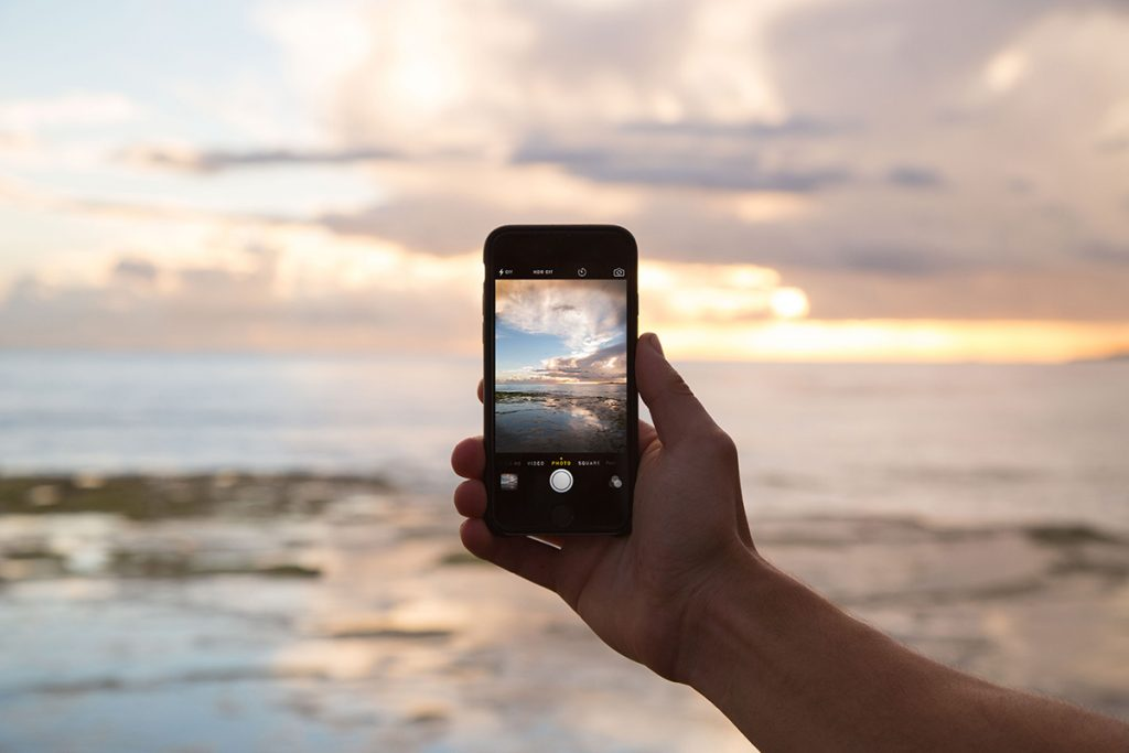 Using a smartphone to capture sunset while travelling