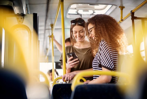 Women using secure public WiFi on a bus