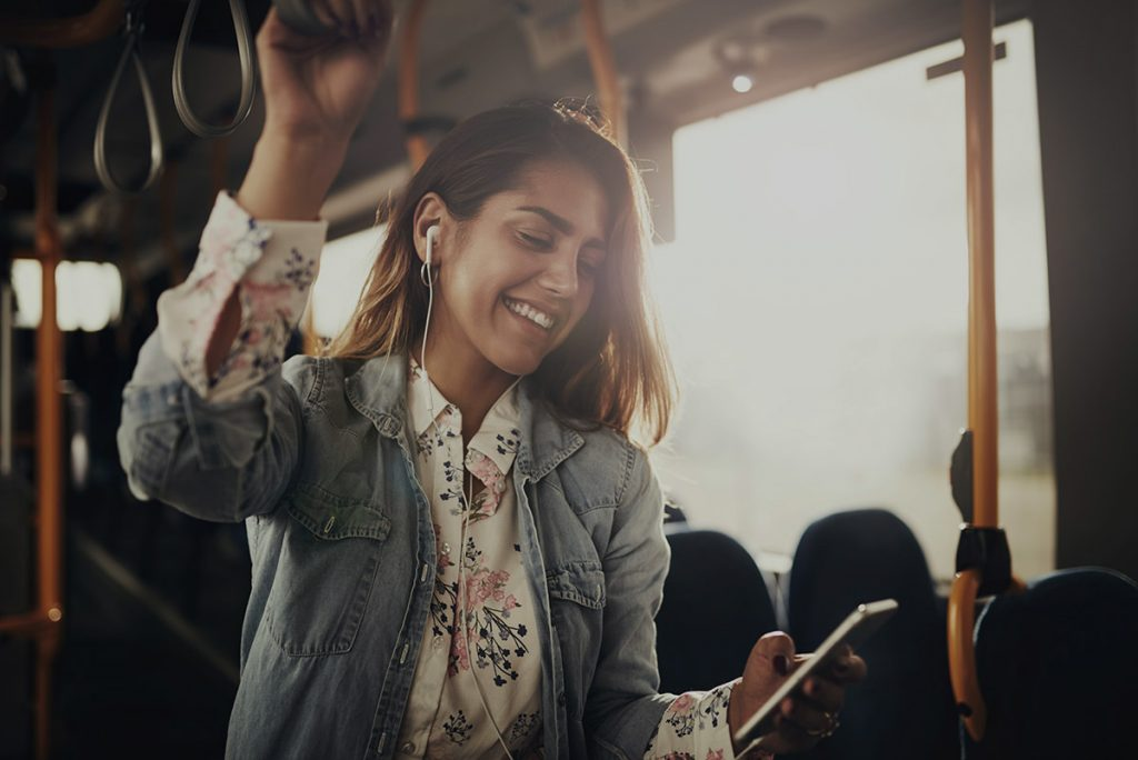 Woman using onboard technologies to browse bus WiFi
