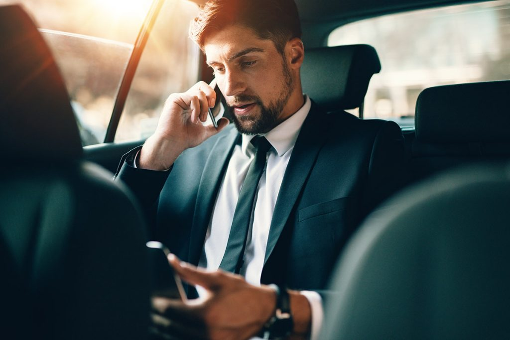 Businessman using in-taxi WiFi on tablet